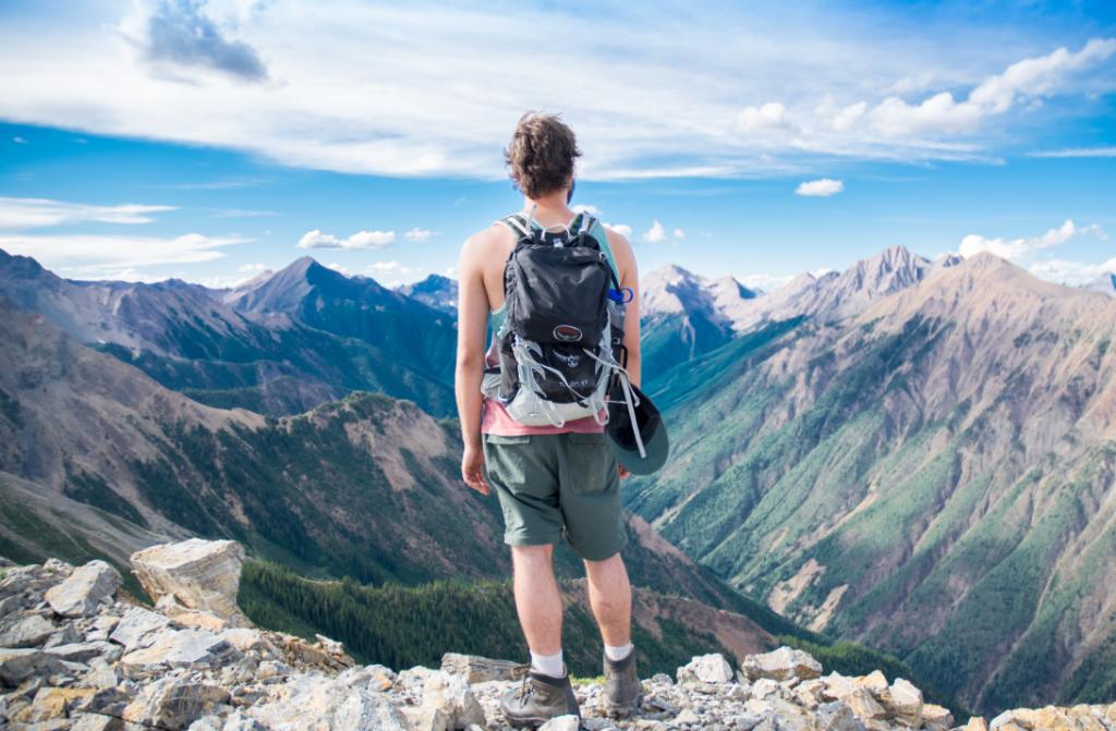 Globe-trotter qui regarde les montagnes à l'horizon