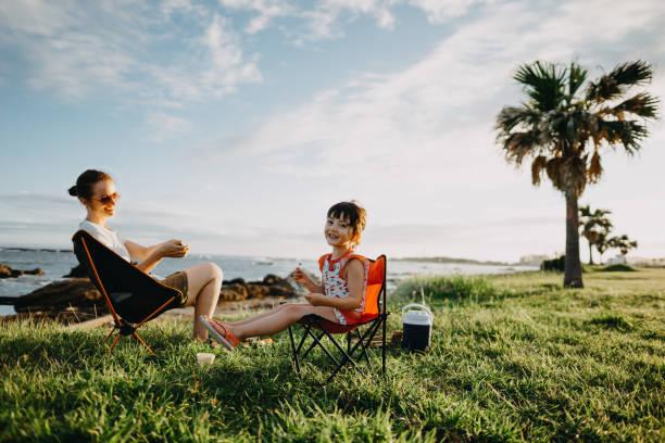 Une femme et sa petite fille assises sur des chaises de camp en pleine nature