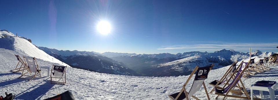 Vue sur une vallée enneigée en montagne avec le soleil et le ciel bleu en fond
